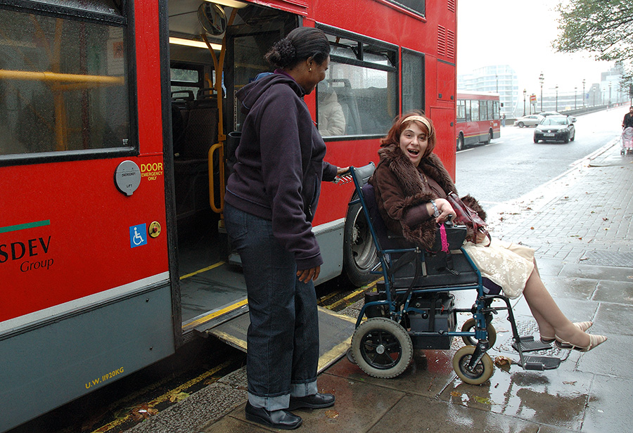 Woman in wheelchair dis-embarking bus.